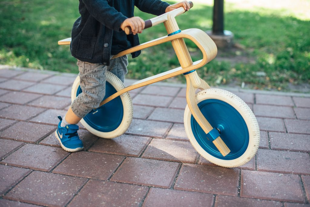 Kid riding balance tricycle.